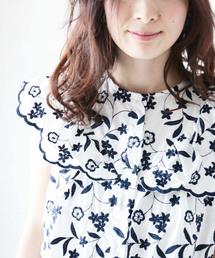 cawaii(カワイイ)のホワイト×ネイビーの可憐な花刺繍のスカラップトップス(シャツ/ブラウス)